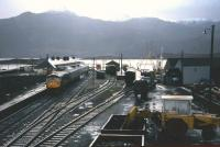 A train for Inverness stands at the platform at Kyle of Lochalsh on a wet Saturday afternoon in November 1982. Freight activities (including coal in the foreground) still survive at this point in time.<br><br>[Frank Spaven Collection (Courtesy David Spaven)&nbsp;20/11/1982]