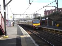 320 306 calls at the Glasgow-bound platform (which seems to need <br> propping-up) at Duke Street on 26 March.� The train has come all of 600 yards from its last stop, Alexandra Parade.� There are two other pairs of stations in Scotland only 27 chains apart.� If you know which they are your knowledge must be its own reward.� The red silos to the right contain flour for British Bakeries which makes bread for the RHM group.<br><br>[David Panton&nbsp;26/03/2011]