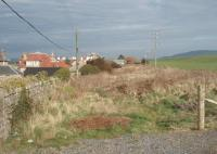 Looking east towards Campbeltown from Machrihanish station site along the old trackbed, which is still clearly visible behind the houses on the main road, almost eighty years after final closure. Further east, where the line crossed farmland, its course is much less well defined and large parts have disappeared altogether. [See image 33498] for a map of the station site and approaches in 1921. <br><br>[Mark Bartlett&nbsp;26/03/2011]