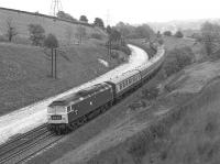 The Harwich Parkeston Quay - Manchester Piccadilly boat <br> train, hauled by 47047, is nearing the end of its journey as it passes through Buxworth cutting, about a mile and a half to the west of Chinley station, in June 1977. The train is formed of early Mk II stock and no doubt a Mk I buffet (in the early seventies it had been one of the last services to employ a Gresley buffet car).<br><br>[Bill Jamieson 11/06/1977]