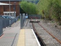 'Lines end' at Maesteg in April 2011, with a detached buffer assembly and chained sleepers acting as a stop barrier. The old trackbed beyond is well used to access Asda and the town using a gap created in the palisade fence behind the trees on the right, and then walking alongside the fence on left to access the platform via the ramp.<br><br>[David Pesterfield&nbsp;20/04/2011]