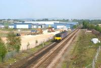 A Northern DMU service heads east towards Chorley on 29 April <br> 2011, passing the site of the new Buckshaw Parkway station. Due to be completed in early October, the new station will be adjacent to the site of the former Chorley Halt [see image 20909]. Work started here early in 2011 and has progressed from the north side of the line (left) where the station building and car park will be located, to the south side, where an access road has been constructed and fencing erected. <br><br>[John McIntyre&nbsp;29/04/2011]