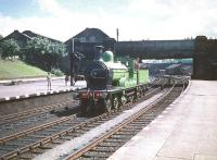 Running through the middle road at Dumfries on 13 June 1959 is ex-Great North of Scotland Railway 4-4-0 No 49 <I>Gordon Highlander</I>. The locomotive has just arrived back in the station following a visit to Dumfries shed for refreshment, having earlier brought in the SLS <I>Golden Jubilee Special</I> from Buchanan Street. No 49 will shortly rejoin the train for the return journey to Glasgow, where the railtour will terminate at St Enoch station. The top of Dumfries shed can be seen in the left background on the south side of St Mary's Street road bridge. [See image 30151]<br><br>[A Snapper (Courtesy Bruce McCartney)&nbsp;/06/1959]