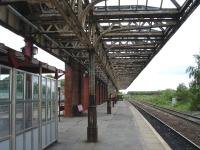 Looking east along platform 3 at Wakefield Kirkgate showing the original canopy, albeit devoid of glass, still in situ on 16 May 2011. At the far end of the former overall roof support wall the canopy also runs fully across platforms 2 & 3. Surveyors can be seen at the far end of the platform. They indicated that the platform was due to be cleared fully to leave just a waiting shelter. Platform 3 is used by the local Pontefract line service plus the three return Grand Central services between Bradford Interchange and London Kings Cross; including the 11.13 service which I was waiting to join. For the same scene 34 years earlier [see image 39219]<br><br>[David Pesterfield&nbsp;16/05/2011]