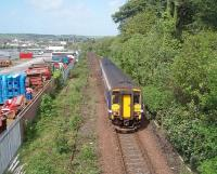 Only a short distance for 156449 to go before reaching Stranraer Harbour as it passes over the disused connection to the Stranraer Town freight facilities. Former railway land to the left of the train is now in other use and Town station is just beyond the white lorry at the end of the yard. Picture taken from overbridge at NX 073604.  <br><br>[Mark Bartlett&nbsp;23/05/2011]