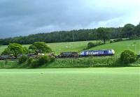A <I>Stobart Rail</I> liveried class 92 locomotive hauling a southbound ballast train on the west coast main line on 24 May 2011. The location is approximately 6 miles north of Lockerbie near the site of the former Dinwoodie station (closed 1960).<br> <br><br>[Bruce McCartney&nbsp;24/05/2011]