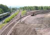 View south over the site of the old down yard at Millerhill on 3 June 2011 with West Coast Railway 57001 passing on the left with the empty stock of <I>The Royal Scotsman</I>. The line curving off to the right is part of the new Borders Railway route heading for what will be its next station at Shawfair. Part of the new Shawfair development will occupy the site of the former Monktonhall Colliery. The short section of new track is currently being used as a replacement turnback siding for trains terminating at Newcraighall. [See image 4433] for the view thirty years earlier.<br> <br><br>[John Furnevel&nbsp;03/06/2011]