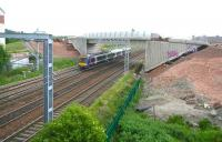 The tram flyover at Saughton looking essentially complete on 31 May 2011 and even possessing its first graffiti. View is from the path up to the footbridge, looking east towards Haymarket, as a Fife bound DMU approaches. [See image 28409]<br><br>[John Furnevel&nbsp;31/05/2011]