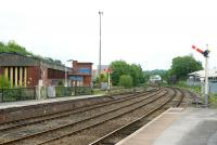 A view of outer station area at Buxton on 4 June 2011. The former BR Buxton diesel depot stands on the left. In the distance is Buxton No 1 Junction signal Box, controlling the station and the line from Stockport. The box also controls two freight lines that come in just out of shot beyond the building on the right and pass by on either side. One of these is the line from Hindlow and the other from Great Rocks/Tunstead.<br> <br><br>[Peter Todd&nbsp;04/06/2011]