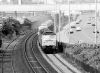 A class 47 accelerates a freight consisting of various new motor vehicles away from Dundee in the summer of 1981. The train is heading east towards Broughty Ferry along the section of line running between the A92 and the docks.<br><br>[John Furnevel&nbsp;11/08/1981]