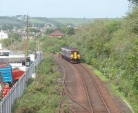 156449 is on the last part of its journey to the Harbour station at Stanraer and just about to swing into the shallow cutting that leads down to the breakwater. Directly above the train the roof of Stranraer steam shed can be seen over the trees [See image 15270] with the disused lines to Stranraer Town to the left.<br><br>[Mark Bartlett&nbsp;23/05/2011]
