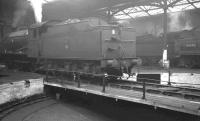 Scene inside Carlisle Canal shed in April 1962. In the picture are J39 0-6-0 no 64895 on the turntable and the rear of Stanier 2-6-4T no 42440 in the background.<br><br>[K A Gray 19/04/1962]