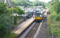 A Class 142 unit calls at Brierfield station with a service to <br> Blackpool South on 9 July 2011. The view is south and at the far end of the platform is the level crossing over the B6248 Clitheroe Road and the signalbox controlling the barriers.<br> <br><br>[John McIntyre&nbsp;09/07/2011]