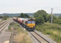 DBS 66013 with a westbound tanker train runs through Pilning station, South Gloucestershire, on 12 July 2011 heading for the Severn Tunnel.<br><br>[Peter Todd&nbsp;12/07/2011]