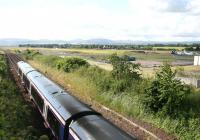 A Dundee - Edinburgh service runs along the eastern perimeter of Edinburgh Airport near the site of Turnhouse station (closed September 1930) on a July afternoon in 2007. The horizon to the south is formed by the Pentland Hills.<br><br>[John Furnevel&nbsp;08/07/2007]