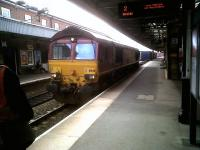 <i>'Please stand clear. Fast train approaching.'</I> So reads the display top right at Nuneaton station on 15 July. However, this Southbound DBS 66-hauled container train then pulled up at the platform for a driver change. That's the new man on the left.<br><br>[Ken Strachan&nbsp;15/07/2011]