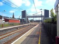 Platform view south at Lockerbie on 3 August, with the towers of the station footbridge and associated lifts, installed in 2008, now competing with the Gothic spire of St Cuthberts Church on Bridge Street, built 136 years earlier.<br><br>[Andrew Wilson&nbsp;03/08/2011]