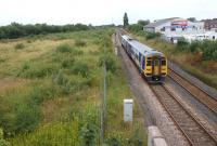 A York - Blackpool service passes the site of the former Lostock <br> Hall station on 3 August 2011. In the wasteland to the left stood Lostock Hall shed. Some clues still remain from the concrete between <br> each road and even the odd bit of rail in the long grass. The photograph was taken from Watkin Lane looking west, with the present day Lostock Hall station behind the camera.<br> <br><br>[John McIntyre&nbsp;03/08/2011]
