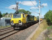 With the <I>Shanks Freightliner</I> liveried 66522 dead in train 70002 powers a rake of Network Rail mega-box ballast wagons south through the closed station of Bay Horse on 9 August. I had spotted this train, thought to be the 6U68 Carlisle Virtual Quarry to Mountsorrel, in Oubeck Up Loop waiting for a Voyager to overtake and just made it to Bay Horse in time to see it pass through. <br><br>[Mark Bartlett 09/08/2011]