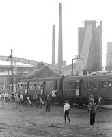 The BLS 'Forth Fife Railtour' stands in front of Alloa glassworks on 28 August 1976. The works stood alongside the branch which left the current main line at Alloa Harbour Junction and ran south to Alloa Ferry passenger station. Alloa Ferry was the original and short lived (June 1851 - July 1852) terminus of the line pending the extension west to Stirling [see image 17758]. The final section of the Harbour branch closed in 1978.<br><br>[Bill Roberton&nbsp;28/08/1976]