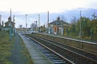 A plethora of poles characterized the station at Westerfield on 26th November 1977 - the station lighting was being upgraded. This was the view east towards the junction with the Felixstowe branch. The manual level crossing gates in the picture were retained for another 13 years.<br><br>[Mark Dufton&nbsp;26/11/1977]