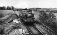 CMHW No.2, a Barclay 0-4-2ST, approaches the hospital station at Whittingham with a train from Grimsargh running along the ash embankment within the hospital grounds. The train consists of three converted LNWR brakevans that were the passenger stock in later years. The photograph dates from prior to 1952 when No 2 was withdrawn and later replaced by the Sentinel locomotive 'Gradwell'. [See image 35479] for the same location in 2011.<br><br>[David Hindle Collection&nbsp;//]