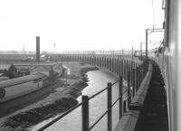 The northern approach arches of the 1868 Runcorn Viaduct carrying the railway across the Mersey between Runcorn and Widnes. Photographed from the LCGB (North West Branch) <i>Two Cities Limited Rail Tour</i> on 23 June 1968. The special, hauled by Stanier 8F 2-8-0 no 48033, has just crossed the river and is starting to turn west towards Liverpool Lime Street with the last leg of the tour from Manchester Victoria. <br><br>[K A Gray&nbsp;23/06/1968]