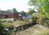 The view into the old railway yard at Whittingham Hospital from the site of the passenger station, the limit of normal passenger services. Although closed in 1957 the bridge that stood in the foreground was only recently removed. Beyond is the old weighbridge house and through the blue fence the former engine shed can be seen. Wagonloads of coal continued beyond the yard through the hospital grounds to the boilerhouse. <br><br>[Mark Bartlett&nbsp;01/09/2011]