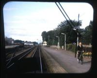 <I>On yer bike!</I> The old order at Nairn in the summer of 1973, as the signalman pedals from the west box back to the token instruments in the station building. Taken from the rear of an Inverness-Aberdeen DMU.<br> <br><br>[David Spaven&nbsp;//1973]