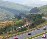 A northbound Pendolino speeds through the Lune Valley towards Tebay on 10 September, passing traffic on the M6 motorway.<br><br>[John McIntyre&nbsp;10/09/2011]