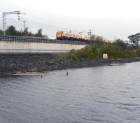 The 12.27 Milngavie - Edinburgh Waverley service approaching Forrestfield through the rain on 19 September 2011. The train is running alongside the east end of Hillend reservoir and will shortly pass the highest point on the line at Holmes Summit [see image 35721].  <br><br>[John Furnevel&nbsp;19/09/2011]