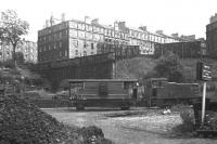 An NBL diesel shunter and brake van at Scotland Street coal depot in mid-1966, a year before closure. The impressive mass of the New Town's Scotland Street dominates the view to the rear, while immediately to the left of the brake van is the bricked-up tunnel which led up the hill to Canal Street station (adjacent, and at right angles to, Waverley). This cable haulage route opened in 1847, and from 1850 to 1868 (when the better graded route via Abbeyhill and Leith Walk stations opened) carried passengers bound for the World's first train ferry, from Granton to Burntisland.<br> <br><br>[David Spaven&nbsp;//1966]