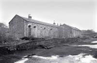 The derelict station building at Penicuik with the goods shed beyond, seen here in December 1976. Closed to passengers in September 1951 the last freight called here in April 1967 [see image 29992]. No trace of the station site remains, with the area shown in the photograph now occupied by a housing development.<br> <br><br>[Bill Roberton&nbsp;/12/1976]