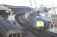 English Electric Class 40 1Co-Co1 No. 40004, one of the ten pilot scheme locos that started life on the Great Eastern main line in 1958, draws a long train out of Holyhead container depot passing the passenger station and an arriving Met-Cam DMU. 40004 continued in main line use for a further three and a half years before withdrawal in September 1984 after twenty six years service. It was cut up at Crewe two years after that.<br><br>[Mark Bartlett&nbsp;15/03/1981]