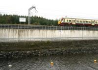 The 12.27 Milngavie - Edinburgh Waverley about to pass the 'Holmes Summit' board alongside Hillend reservoir, between Caldercruix and Blackridge, on 19 September 2011 [see image 35721].  <br><br>[John Furnevel&nbsp;19/09/2011]
