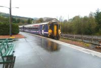 A train from Glasgow Queen Street runs into a wet Crianlarich station on 4 October 2011. The disused timber loading sidings stand in the background. A study is currently underway into the feasibility of reinstating timber loading facilities at Crianlarich, either from an upgraded railhead here, or on the truncated line to the former Crianlarich Lower.  [See image 8732] <br> <br><br>[Bruce McCartney&nbsp;04/10/2011]