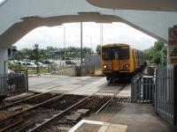 A West Kirby to Liverpool service slows for its first call at Hoylake. 508141 approaches the art-deco station [See image 34460] over the level crossing and under the concrete footbridge.<br><br>[Mark Bartlett&nbsp;11/06/2011]