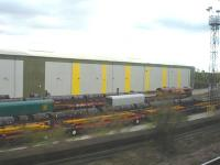 Passing shot showing a fairly crowded Wolverhampton steel terminal on 12 October, with various loads of plate, section and coil visible in the sidings. DBS 66238 stands in the right background, with hooded rail wagons beyond at the far end of the transit shed.  <br><br>[David Pesterfield&nbsp;12/10/2011]