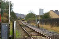 A Blackpool South to Colne service approaches Chaffers Crossing east of Nelson station on 21 October 2011. The driver will bring the train to a stand with the cab window next to the board on the right and pull the cord to initiate the closing of the barriers [see image 17268].<br> <br><br>[John McIntyre&nbsp;21/10/2011]