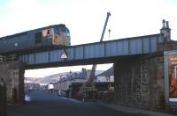 View north along Lower Kessock Street in the Merkinch district of Inverness in 1977 as a class 26  is about to cross with a train from the north. Preparatory work in connection with the replacement of the bridge deck  is taking place in the background. [With thanks to all who responded to this query]<br> <br><br>[Frank Spaven Collection (Courtesy David Spaven)&nbsp;//1977]