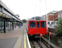 A District Line shuttle service stands in the bay at Kensington Olympia on 24 July 2005. It will shortly undertake the short return journey to High Street Kensington via Earls Court. The Olympia Exhibition Centre stands on the right.  <br><br>[John Furnevel&nbsp;24/07/2005]