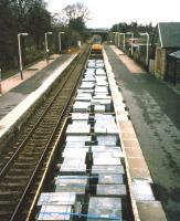 A class 37-hauled freight special conveying flagstone paving from Georgemas Junction to Kyle of Lochalsh drifts through the platforms of Tain station in 1997. [See image 38387]<br><br>[David Spaven Collection&nbsp;//1997]