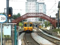 A Tyne and Wear Metro service bound for Newcastle heads north shortly after leaving St Peters station on the north bank of the River Wear in 2004. The train is running through the abandoned platforms of the 1848 Monkwearmouth station and is about to pass an approaching service heading for South Hylton.<br><br>[John Furnevel&nbsp;10/07/2004]