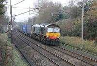 DRS 66421 hustles the 4M44 Mossend to Daventry containers south towards the closed station at Barton and Broughton. On this gloomy November afternoon the dark blue livery appeared almost black.<br><br>[Mark Bartlett&nbsp;15/11/2011]