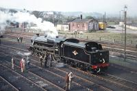 After visiting Ravenglass on 9 May 1970, Scottish Grand Tour No. 10 retraced its steps to Carnforth, where enthusiasts were able to visit Steamtown. Photograph taken from the footbridge giving access off Warton Road, showing preserved Black 5 No. 44871 in steam in the shed yard. [Railscot note: By coincidence the young man in the brown coat to the left of the small  group alongside the cab is Railscot contributor Jim Peebles!]  <br><br>[Bill Jamieson&nbsp;09/05/1970]