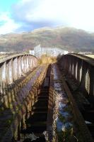 Looking across the old rail bridge over the River Devon on 12 November 2011. View north through a gap in the metal fence towards Menstrie, with the Ochil Hills beyond.<br><br>[Grant Robertson&nbsp;12/11/2011]