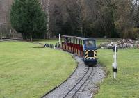 There are three miniature lines at the excellent Conwy Valley Railway Museum and this is the longest with two out and back loops making a circuit that takes ten minutes to complete. The line is fully signalled for an intensive summer service but only one train was required on 1st December. Diesel locomotive <I>Gwydir Castle</I> is seen here just crossing the bridge over the water feature with the Blaenau Ffestiniog branch in the background.<br><br>[Mark Bartlett&nbsp;01/12/2011]