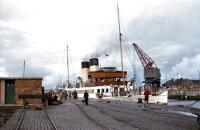 Scene on the south side of Ayr harbour in September 1955 with TS <I>Duchess of Hamilton</I> berthed in her usual place. Built for the Caledonian Steam Packet Company by Harland and Wolff at Govan, she was the regular Ayr steamer and had been fitted with a bow rudder (the wheel is just visible on the foredeck) to assist movements at Ayr, which was difficult to enter under certain conditions. The railway sidings here were reached from the goods station located to the north of the harbour via a now-dismantled bridge, the piers of which still stand in the river. [See image 45697]<br><br>[A Snapper (Courtesy Bruce McCartney)&nbsp;09/09/1955]