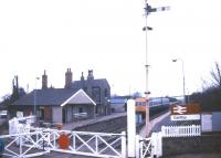 Looking over the level crossing at Cantley, Norfolk, as the gates are reopened in January 1988 with a DMU standing at the platform. View is north west towards Norwich. <br><br>[Ian Dinmore&nbsp;13/01/1988]