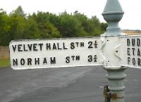 A remote crossroads in Northumberland, in 2006. The recently painted sign directs the motorist back in time to Velvet Hall Station closed 1955) and Norham Station (closed 1964). The line from Tweedsmouth to Kelso closed completely in 1965. [See image 37085]<br><br>[Brian Taylor&nbsp;//2006]